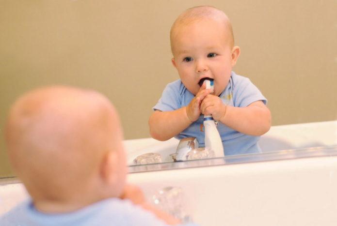Kind reinigt die Zähne